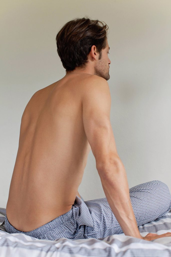 Stock Photo: 1569R-9079219 Man sitting on bed, rear view