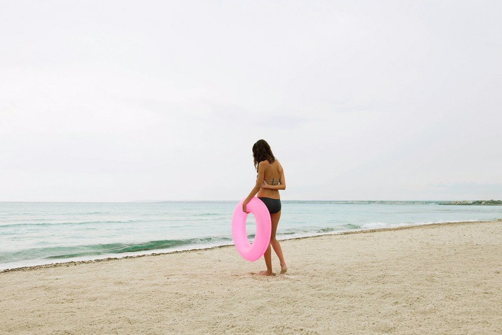 Stock Photo: 1569R-9079472 Woman standing on beach, holding inflatable ring, rear view