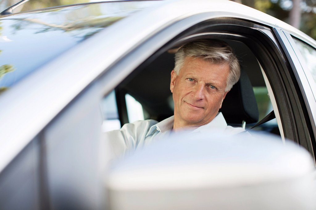 Stock Photo: 1569R-9079492 Man driving car, looking out window at camera
