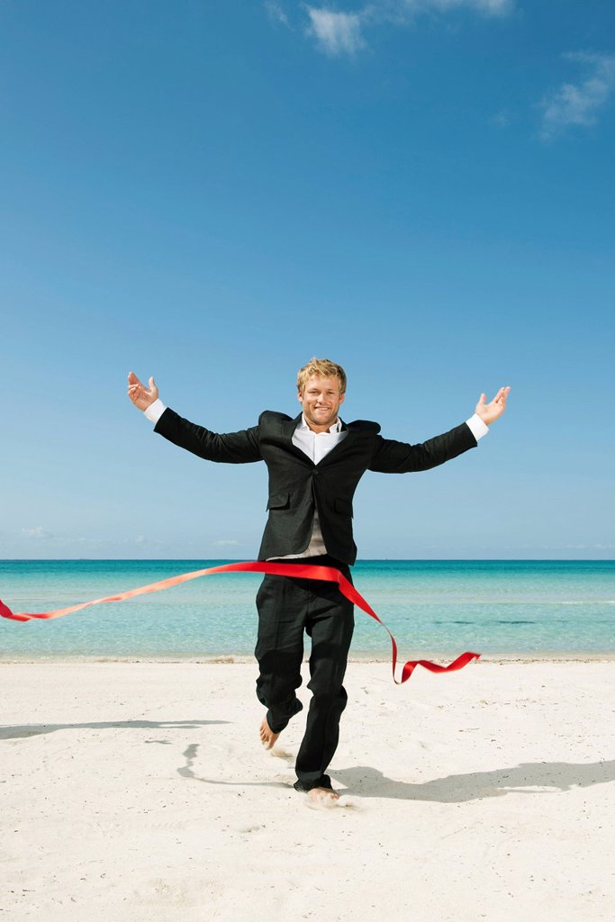 Stock Photo: 1569R-9079496 Young businessman running on beach towards finishing line