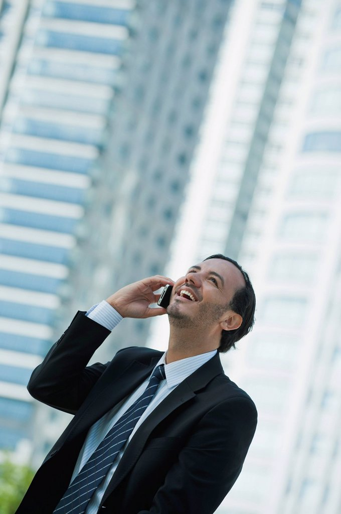 Business executive using cell phone outdoors : Stock Photo