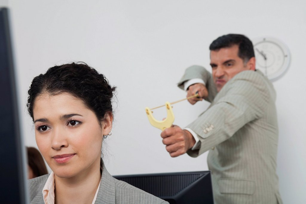Stock Photo: 1569R-9079559 Businessman aiming slingshot at young female colleague