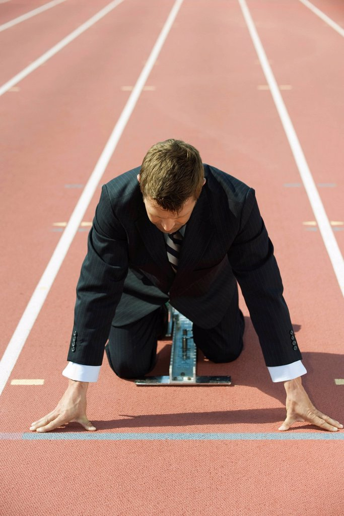 Stock Photo: 1569R-9079608 Businessman crouching at starting line on running track
