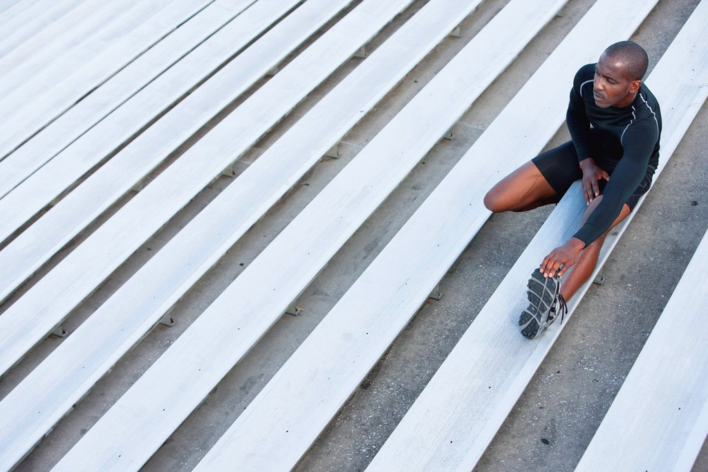 Stock Photo: 1569R-9079642 Man stretching on bleacher, high angle view