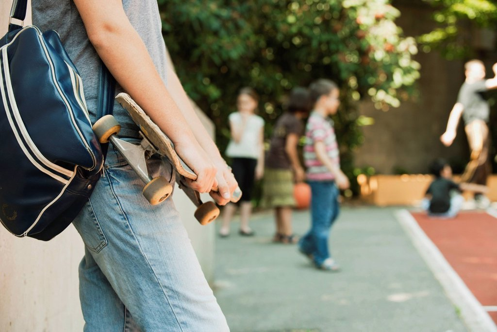 Stock Photo: 1569R-9079666 Man holding skateboard, mid section