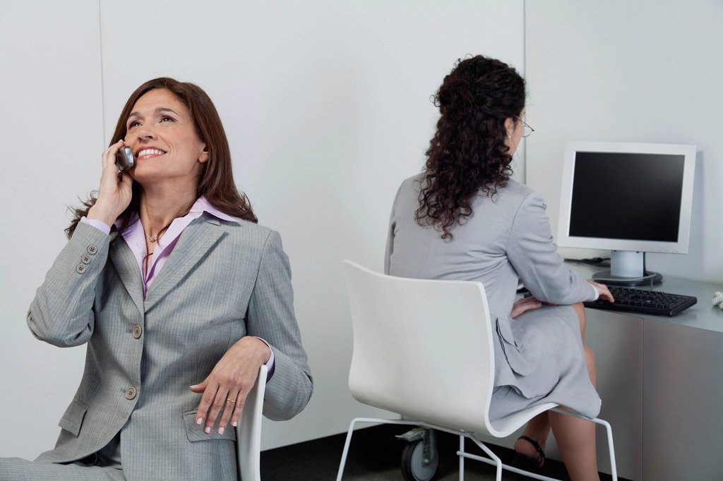 Businesswoman idly chatting on cell phone while colleague works nearby : Stock Photo