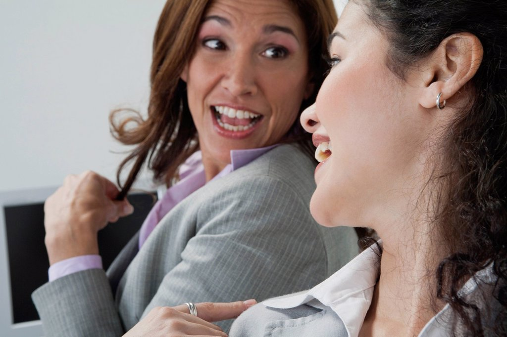 Female coworkers chatting in office : Stock Photo
