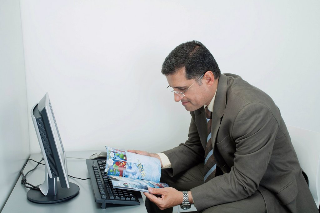 Mature man reading comic book in office cubicle : Stock Photo