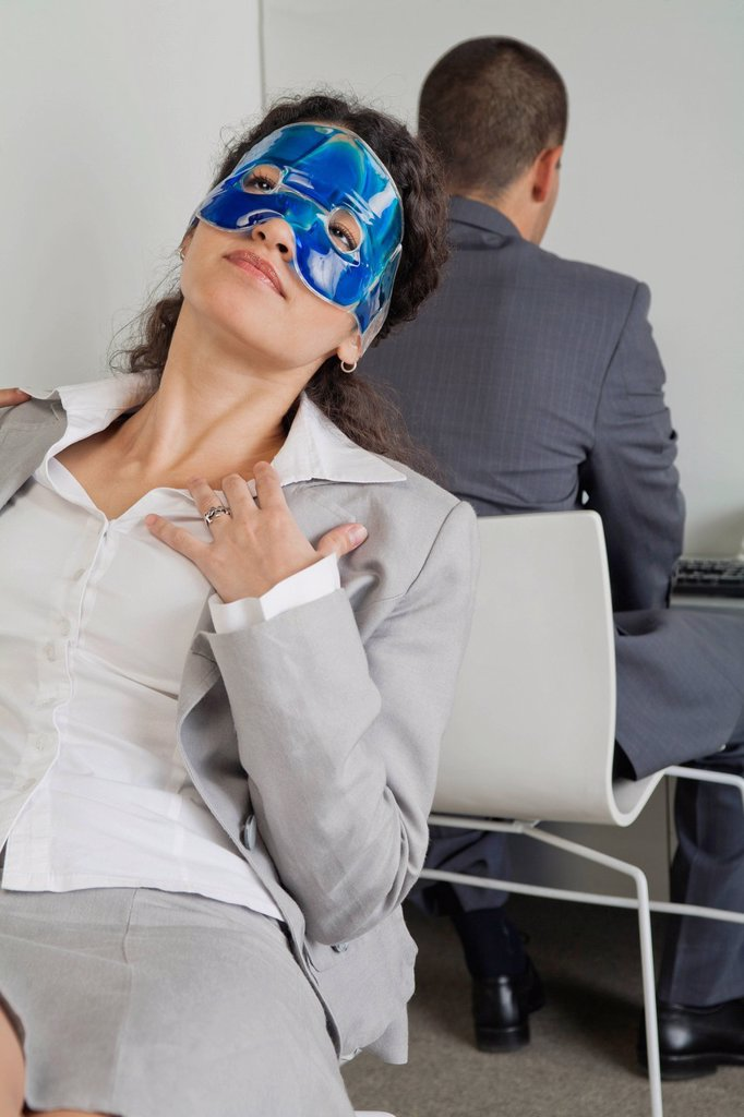 Woman relaxing with eye mask in office as colleague works nearby : Stock Photo