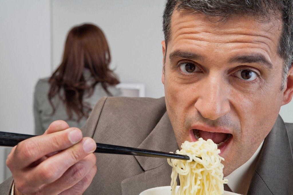 Stock Photo: 1569R-9079895 Mature businessman eating ramen noodles in office