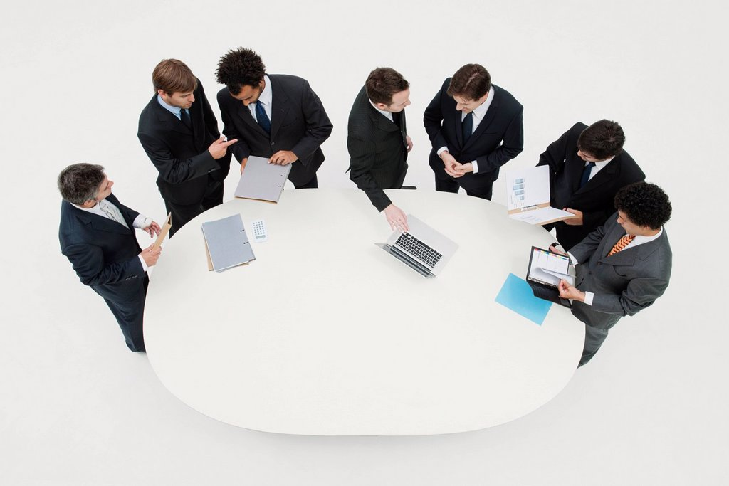 Business associates working together in pairs around table : Stock Photo
