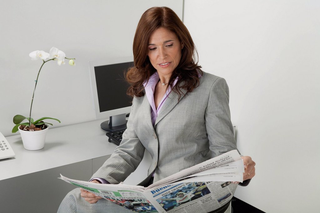 Stock Photo: 1569R-9080025 Mature businesswoman reading newspaper in office
