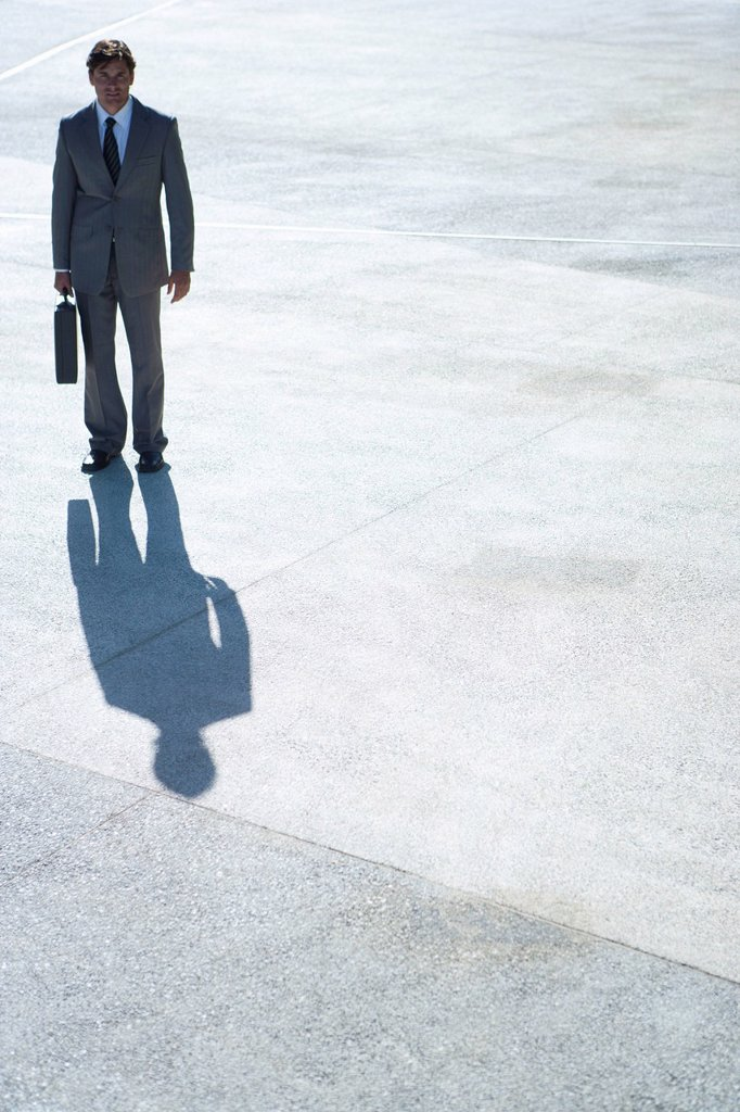 Businessman standing outdoors with briefcase in hand : Stock Photo