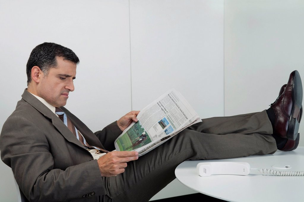 Stock Photo: 1569R-9080046 Businessman reading newspaper in office with feet up on desk