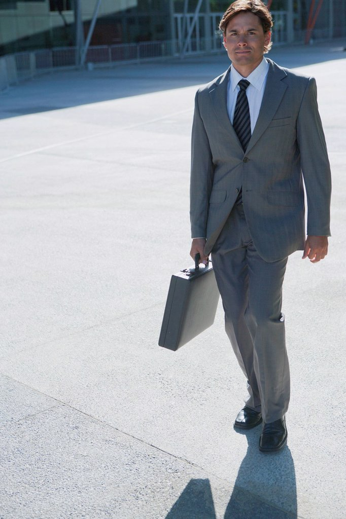 Stock Photo: 1569R-9080047 Businessman walking outdoors with briefcase in hand