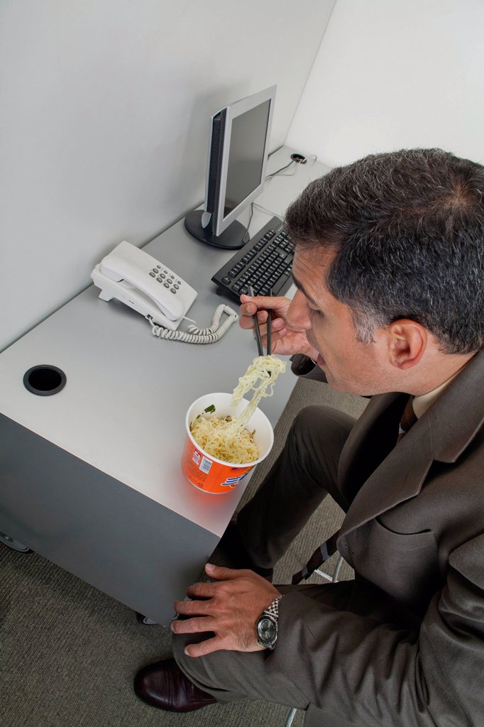 Stock Photo: 1569R-9080066 Businessman eating ramen noodles at desk in office