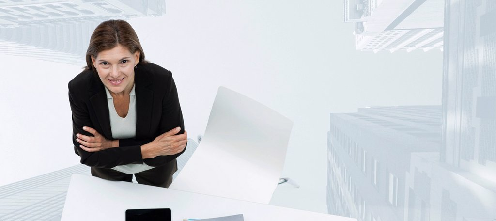 Stock Photo: 1569R-9080101 Mature businesswoman smiling confidently with skyscrapers superimposed on background