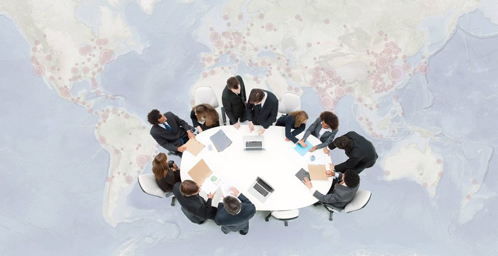 Stock Photo: 1569R-9080165 Business executives meeting on top of superimposed world map