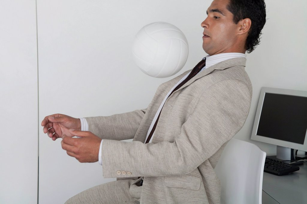 Stock Photo: 1569R-9080249 Man playing with ball in office