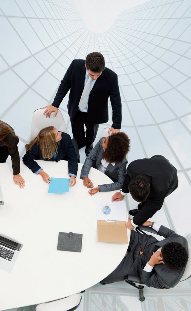Stock Photo: 1569R-9080259 Business associates in meeting on top of superimposed skyscraper image