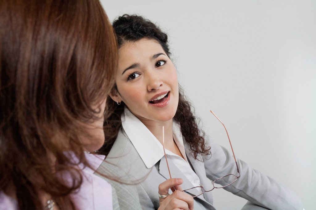 Female colleagues talking together in office : Stock Photo
