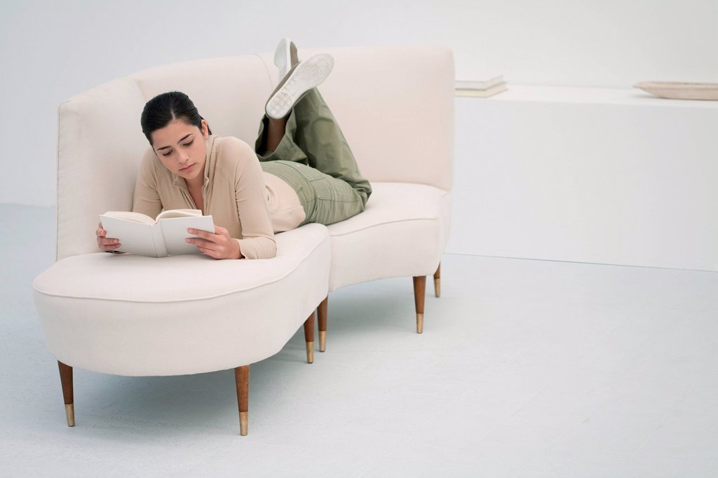 Stock Photo: 1569R-9080299 Young woman lying on chaise longue, reading book