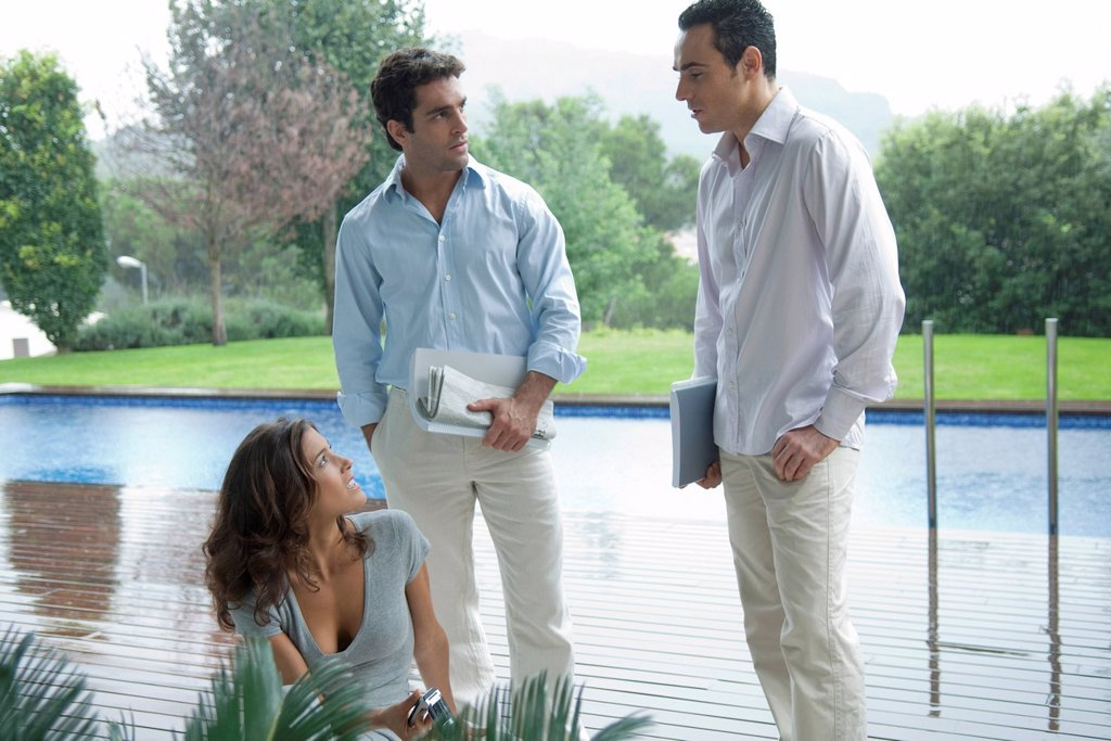 Stock Photo: 1569R-9080362 Casually dressed executives having poolside meeting