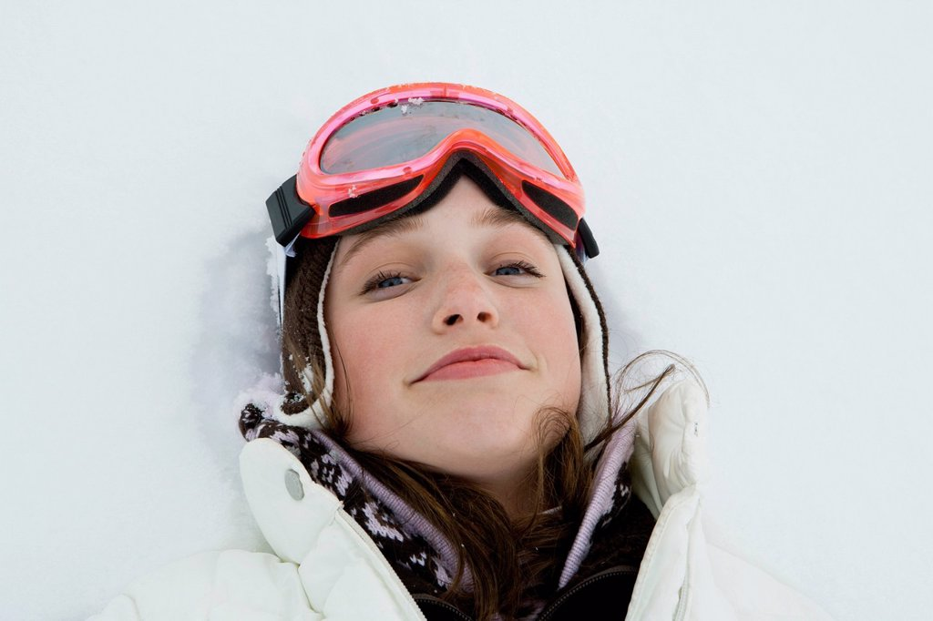Teenage girl in ski outfit lying in snow : Stock Photo