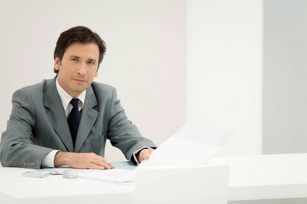 Stock Photo: 1569R-9080450 Business executive reviewing documents, portrait