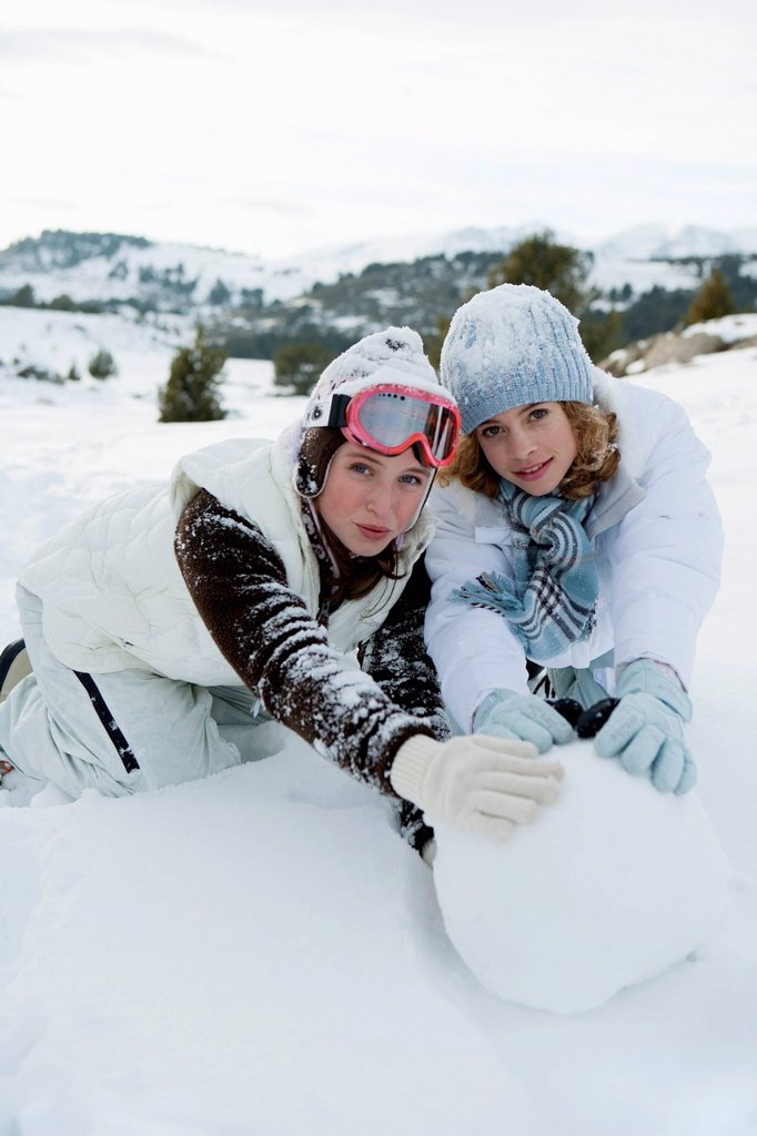 Stock Photo: 1569R-9080490 Teenage girls rolling snowball together, portrait