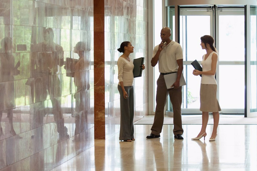 Stock Photo: 1569R-9080517 Colleagues talking in lobby, backlit