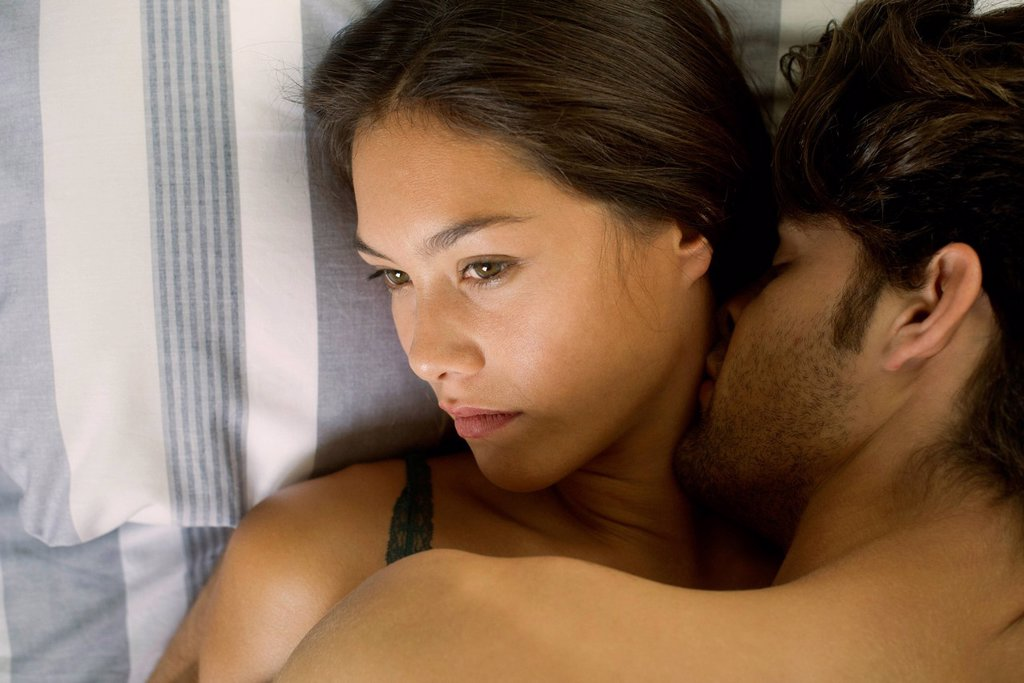 Stock Photo: 1569R-9080534 Young couple being intimate in bed, woman looking disinterested