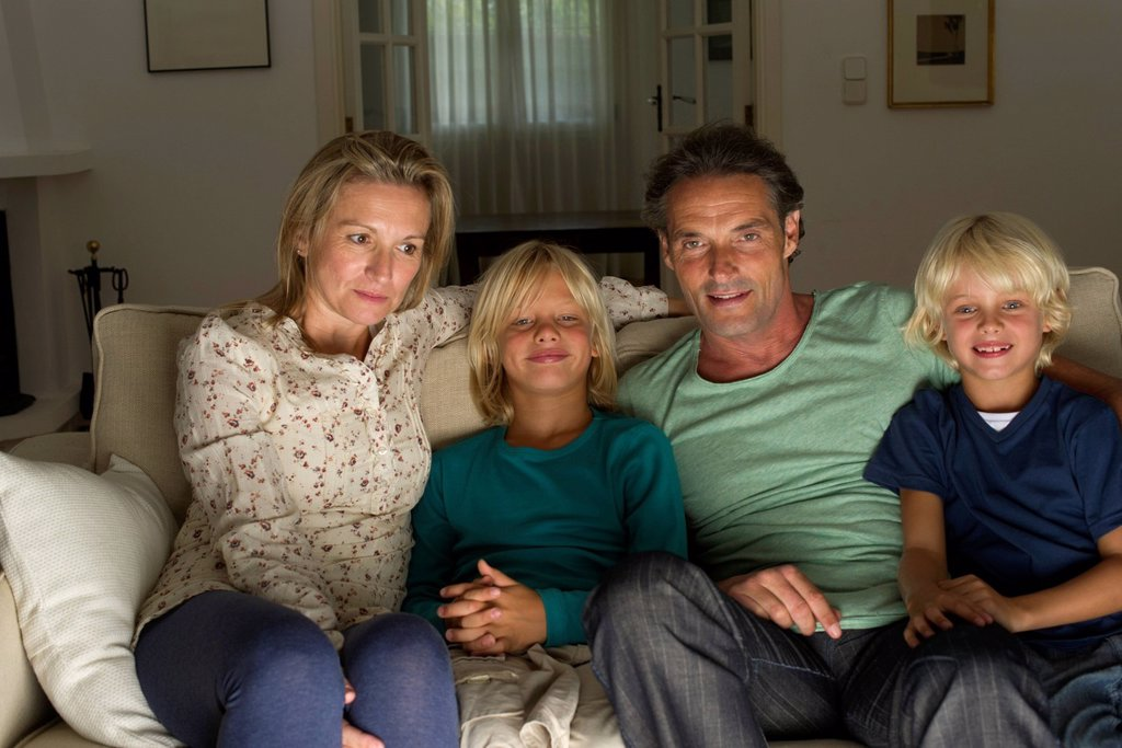 Family sitting together on sofa, watching TV : Stock Photo