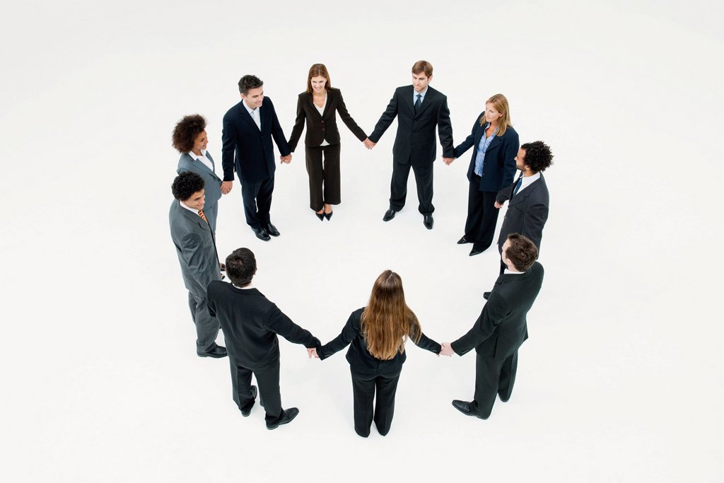 Businessmen and businesswomen standing together in circle holding hands : Stock Photo