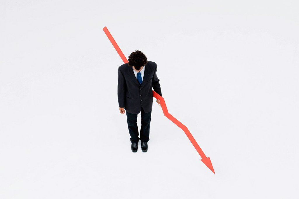 Stock Photo: 1569R-9080656 Businessman with arrow pointed downward, projecting financial loss