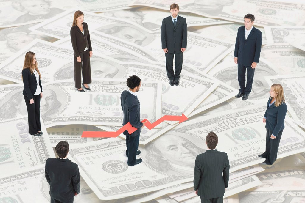 Executives standing on large pile of money around man holding arrow forecasting financial future : Stock Photo