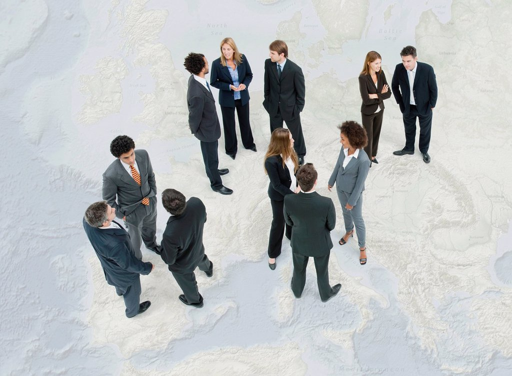 Stock Photo: 1569R-9080708 Executives chatting while standing on map of Europe