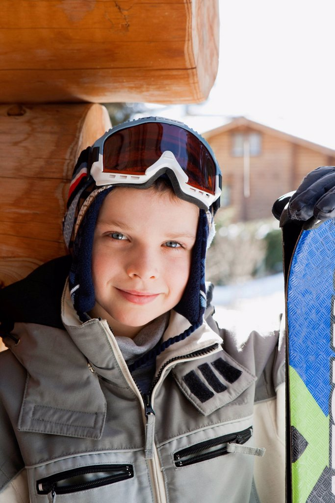 Stock Photo: 1569R-9080789 Boy wearing ski goggles and ski jacket and holding snowboard, portrait