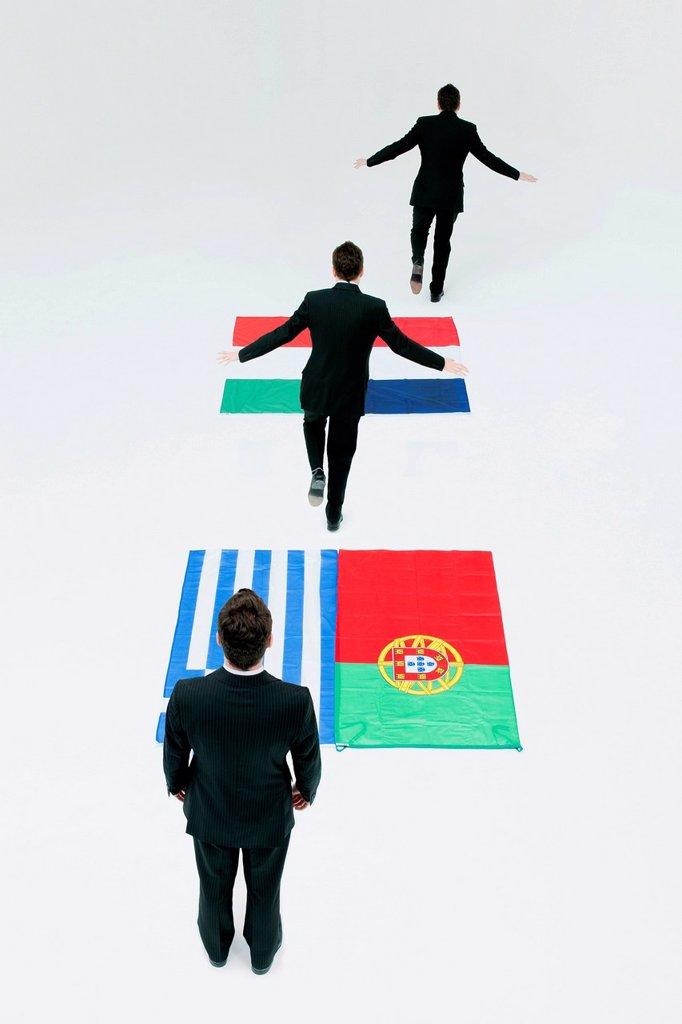 Stock Photo: 1569R-9080874 Businessman running across Greek, Portuguese, Italian and French flags