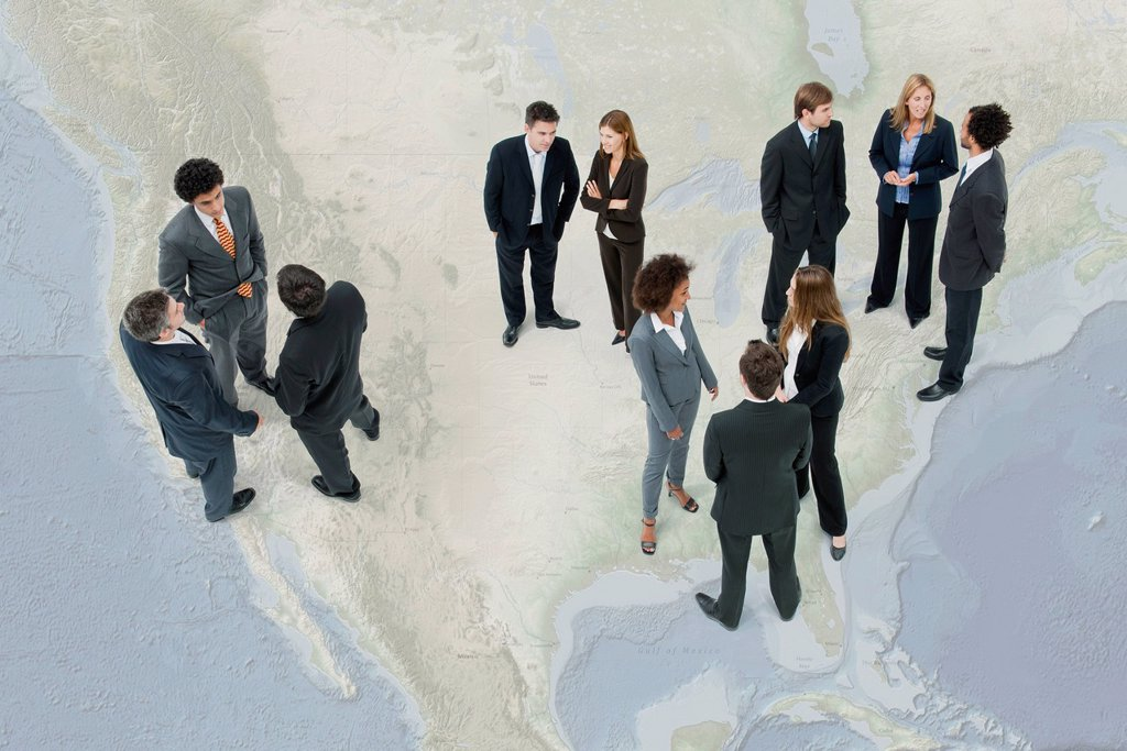 Stock Photo: 1569R-9080875 Executives chatting while standing on map of the United States