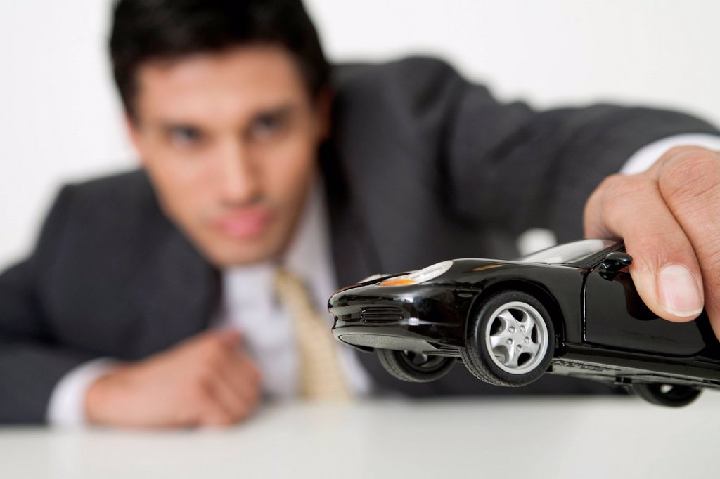 Stock Photo: 1569R-9081298 Mid-adult businessman playing with toy car