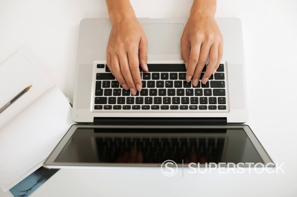 Hands typing on laptop computer, high angle view : Stock Photo