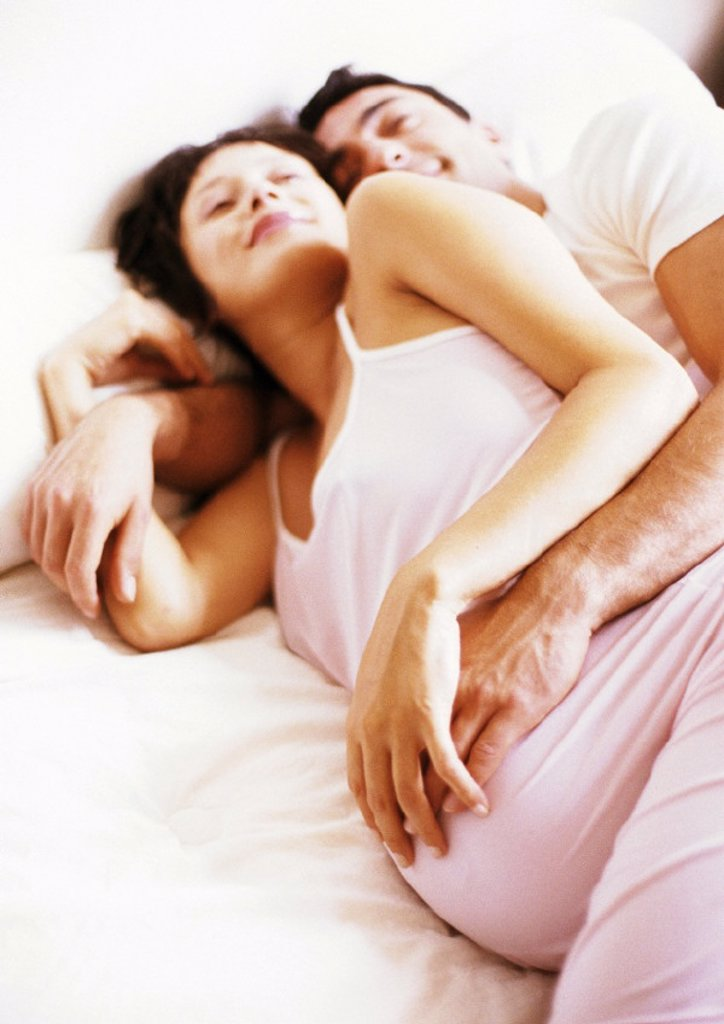 Stock Photo: 1569R-93026 Man embracing pregnant woman in bed