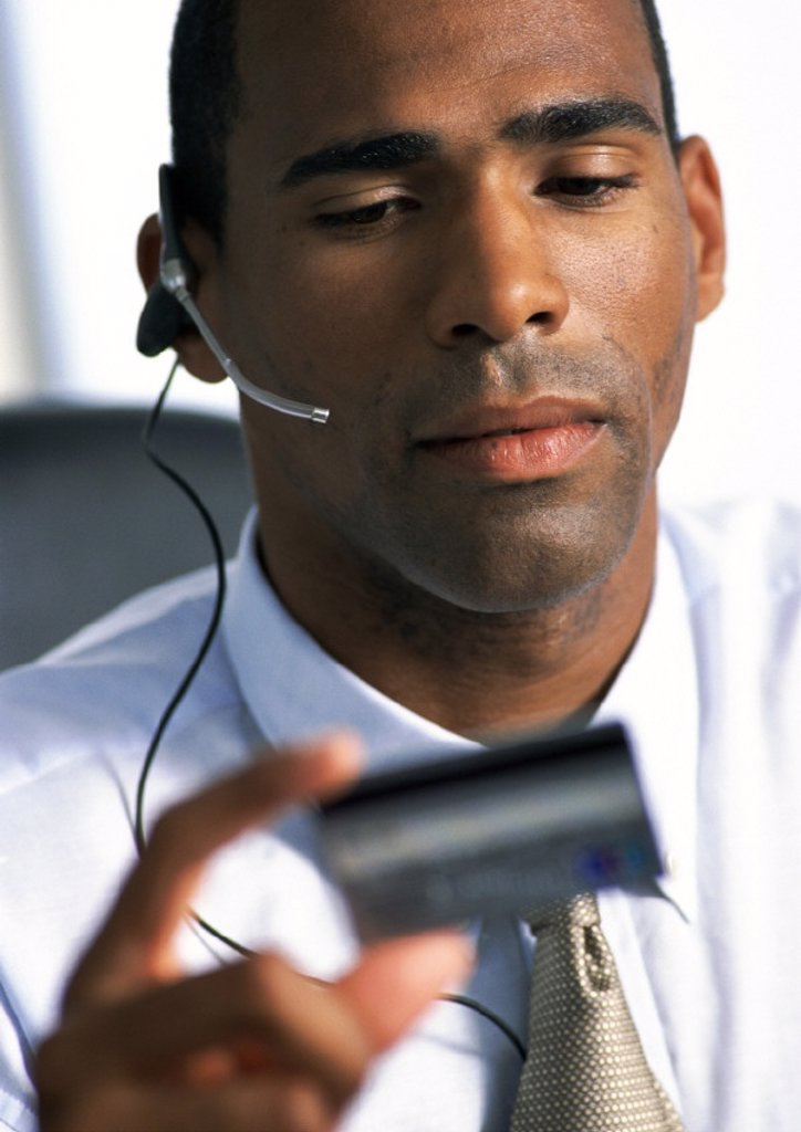 Businessman wearing headset, looking down at credit card in hand, close-up : Stock Photo