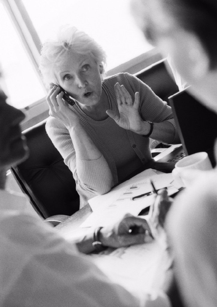 Stock Photo: 1569R-94059 Mature businesswoman using cell phone, colleagues in blurred foreground, B&W
