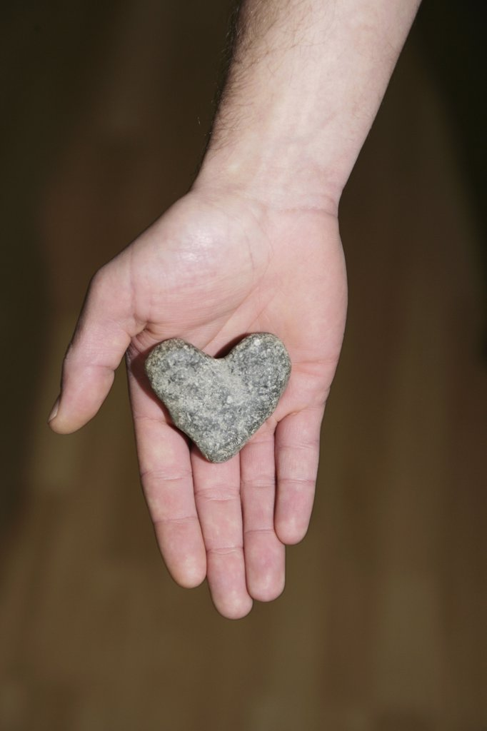 Stock Photo: 1570R-0957 Heart shaped stone in man's hand