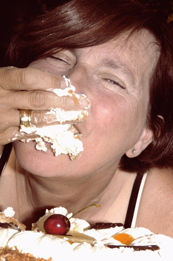 Stock Photo: 1570R-100130 Woman eating cake with hand