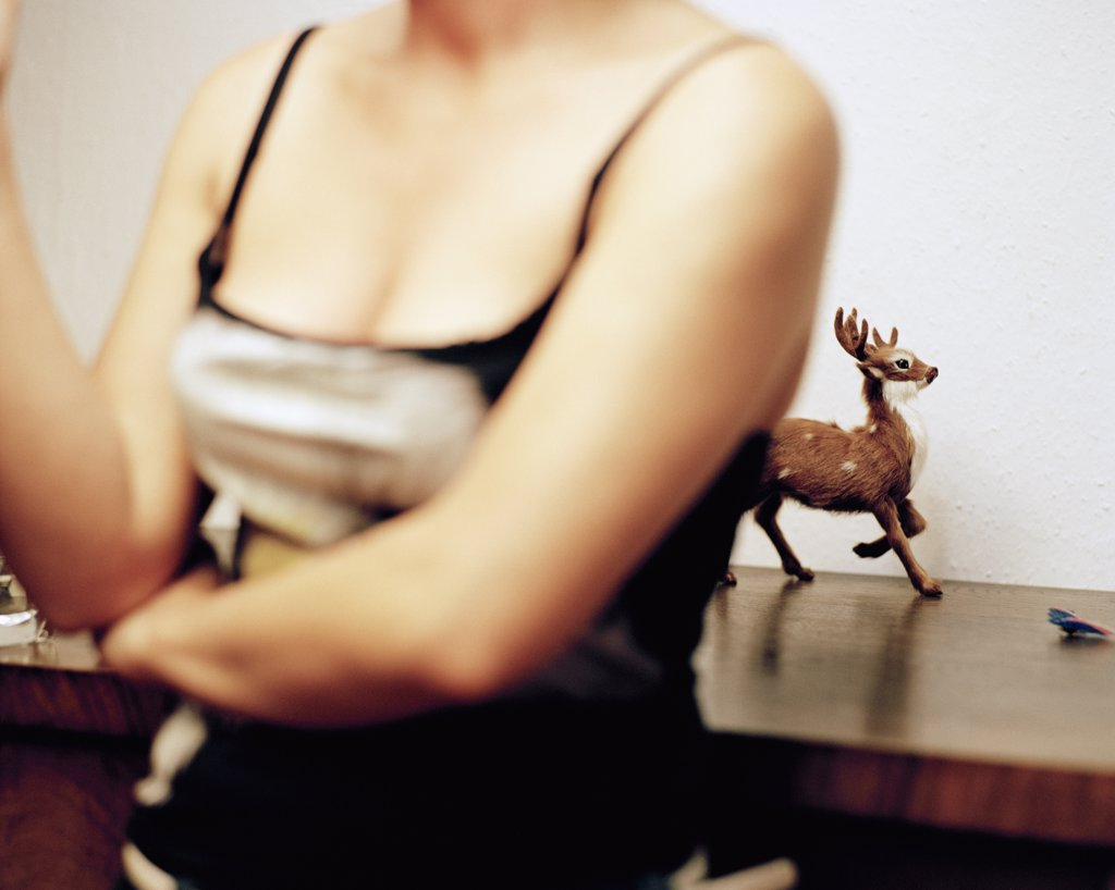 Woman standing in front of a reindeer figure : Stock Photo