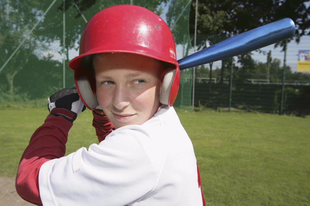A boy in a baseball uniform holding a baseball bat : Stock Photo