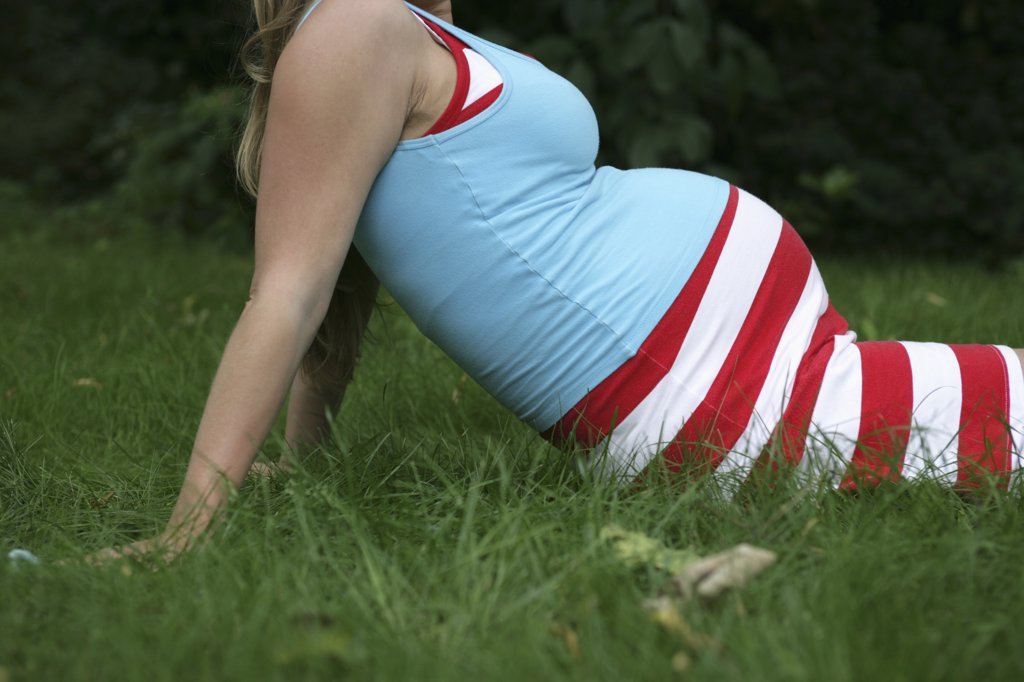 Stock Photo: 1570R-102180 A pregnant woman relaxing in the grass